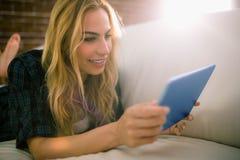 Recht blonde Entspannung auf der Couch unter Verwendung der Tablette Lizenzfreie Stockfotos