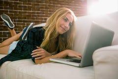 Recht blonde Entspannung auf der Couch unter Verwendung des Laptops Stockbilder