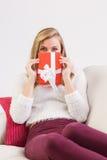 Recht blonde Entspannung auf Sofa mit Geschenk Lizenzfreie Stockfotos