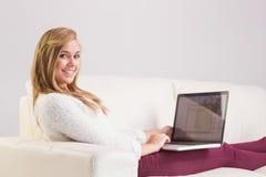 Recht blonde Entspannung auf Sofa mit Laptop Lizenzfreies Stockbild