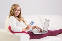 Recht blonde Entspannung auf Sofa mit Laptop Lizenzfreie Stockfotografie