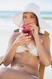Recht blonde Entspannung im Klappstuhl auf dem Strand mit Cocktail Lizenzfreie Stockfotografie