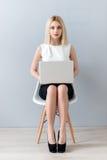 Recht blonde Frau benutzt einen Computer Stockfoto