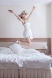 Recht blonde Frau in den Tüchern springen auf großes Bett Stockfotografie