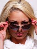 Recht blonde Frau, die über ihren Gläsern schaut Lizenzfreie Stockbilder