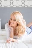 Recht blonde Frau, die in anfälligem auf Bett liegt Stockfotos