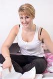 Recht blonde Frau, die auf Bett mit einem Buch sitzt Stockfoto