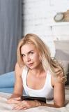 Recht blonde Frau, die auf Bett mit Tablette liegt Lizenzfreie Stockfotos