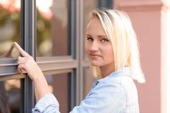 Recht blonde Frau, die auf ein Fenster zeigt Stockbild
