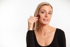 Recht blonde Frau, die auf Gesichtspuder sich setzt Stockbilder