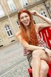 Recht blonde Frau, die auf rotem Stuhl sitzt Stockbild