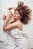 Recht blonde Frau, die in Bett auf weiße Scheiße legt Lizenzfreies Stockfoto