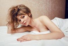 Recht blonde Frau, die in Bett auf weiße Scheiße legt Lizenzfreie Stockbilder