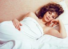 Recht blonde Frau, die in Bett auf weiße Scheiße, sexy Blick römisch legt Stockfotografie