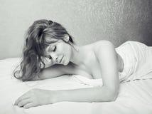 Recht blonde Frau, die in Bett auf weiße Scheiße, sexy Blick romantisch legt Stockfotos
