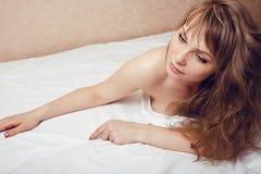 Recht blonde Frau, die in Bett legt Stockbilder
