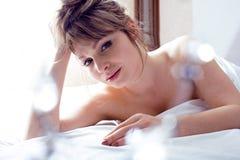Recht blonde Frau, die in Bett legt Lizenzfreies Stockfoto