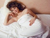 Recht blonde Frau, die in Bett legt Stockbild