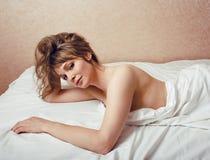Recht blonde Frau, die in Bett legt Stockfotografie
