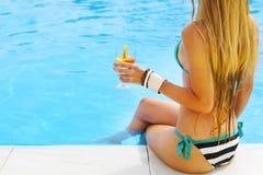 Recht blonde Frau, die Cocktail nahe dem Swimmingpool genießt Stockfoto