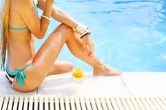 Recht blonde Frau, die Cocktail nahe dem Swimmingpool genießt Lizenzfreie Stockfotos