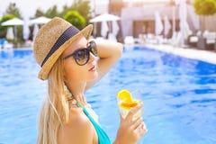 Recht blonde Frau, die Cocktail nahe dem Swimmingpool genießt Stockfotografie