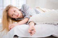 Recht blonde Frau, die das Lügen im Bett aufwacht Lizenzfreies Stockfoto