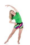 Recht blonde Frau, die in der Sportkleidung losstürzt und kippt zur Seite mit der Hand über einem Kopf trägt Stockbilder