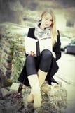 Recht blonde Frau, die draußen ein Buch liest Stockfotografie