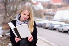 Recht blonde Frau, die draußen ein Buch liest Stockbilder