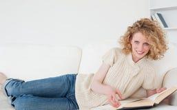 Recht blonde Frau, die ein Buch beim Lügen liest Stockbild