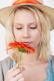Recht blonde Frau, die eine Blume riecht Stockfoto