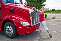 Recht blonde Frau, die eine LKW-Haube öffnet. Stockfoto