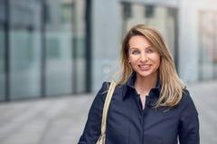 Recht blonde Frau, die in eine städtische Straße geht Stockfotos