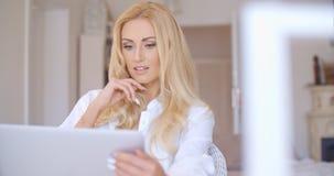 Recht blonde Frau, die ernsthaft ihren Laptop betrachtet Lizenzfreies Stockbild