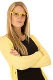 Recht blonde Frau, die gelbe Gläser mit den Armen gefaltet trägt Lizenzfreie Stockfotografie