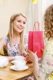 Recht blonde Frau, die Geschenk im Café erhält Lizenzfreie Stockfotos