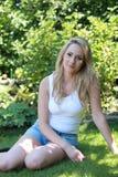 Recht blonde Frau, die in ihrem Garten sich entspannt Lizenzfreies Stockbild