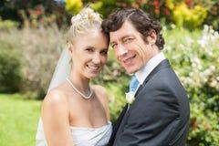 Recht blonde Frau, die ihren neuen Ehemann lächelt an der Kamera umarmt Stockfotografie