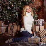 Recht blonde Frau, die Kästen mit Geschenken unter Weihnachtsbaum hält Weihnachten und neues Jahr Lizenzfreies Stockfoto