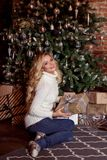 Recht blonde Frau, die Kästen mit Geschenken unter Weihnachtsbaum hält Weihnachten und neues Jahr Stockfotografie