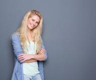 Recht blonde Frau, die mit den Armen gekreuzt lächelt Lizenzfreies Stockfoto