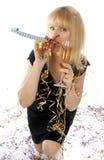 Recht blonde Frau, die mit einem Glas Champagner auf dem Silvesterabend mit Geräuschhersteller feiert Stockfotografie