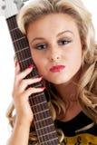 Recht blonde Frau, die mit Gitarre aufwirft Lizenzfreie Stockfotos