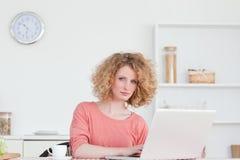 Recht blonde Frau, die mit ihrem Laptop sich entspannt Stockfotografie
