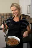 Recht blonde Frau, die Nahrung kocht Stockbilder