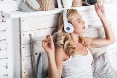 Recht blonde Frau, die zu Hause Musik hört Stockfotos