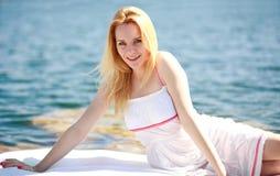 Recht blonde Frau in einem weißen Kleid auf Hintergrund des blauen Wassers Stockfoto