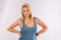 Recht blonde Frau im blauen Hemd, die Kamera betrachtend Stockfotografie