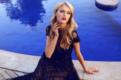 Recht blonde Frau im eleganten Spitzekleid, das neben einem Swimmingpool aufwirft Stockbilder